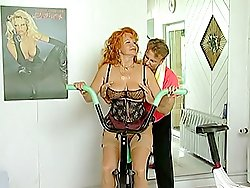 Big-breasted mature redhead in sexy lingerie seduces her handsome fitness coach and gets fucked right in a gym