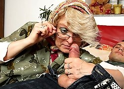 Smart looking granny in glasses goes for the cock of the horny young man