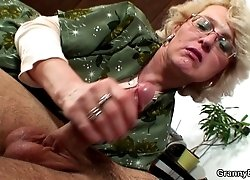 The old babe gives him a handjob and lets him nail her wet pussy from behind