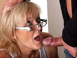 The hot granny wears glasses and eats a big fat cock to make her man happy as can be