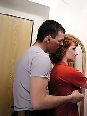Redhead MILF and her young lover having fun right at the front door of their apartment